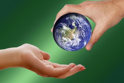 Slika prikazuje planet Zemlja v človeških rokah.