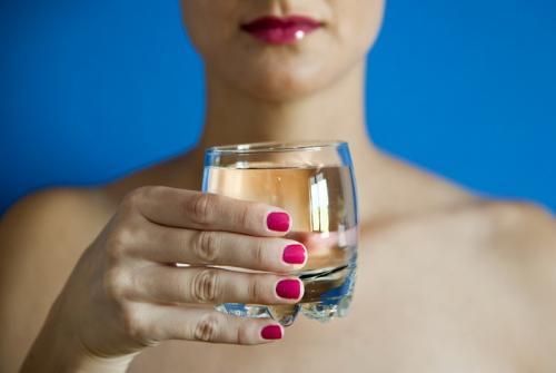 Kozarec z vodo v ženski roki.