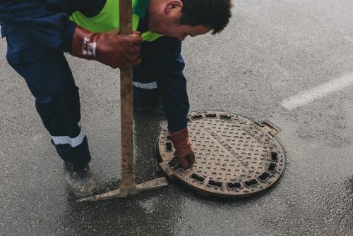 Slika prikazuje delavca, ki odpira kanalizacijski jašek.