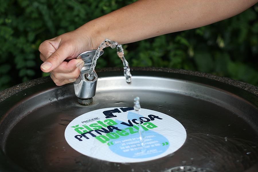 Slika prikazuje pitnik z nalepko poezija vode.
