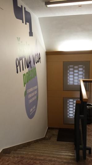 Slika prikazuje steno z logotipom poezija vode na sedežu podjetja.